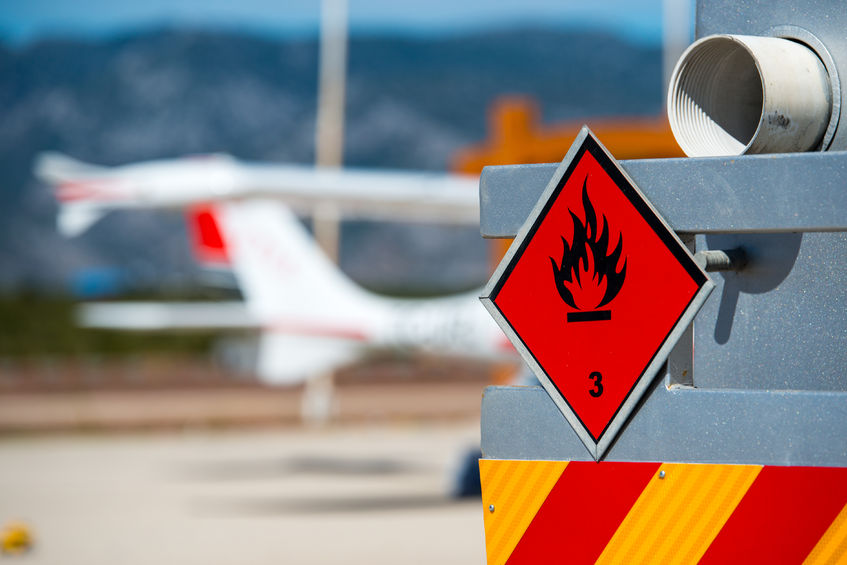 73893871 - rear view of service and refuelling truck on an airport with an aircraft in the blurry background. chemical hazard, flammable liquids.